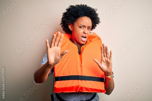 Photo Young African American afro woman with curly hair wearing orange protection lifejacket disgusted expression, displeased and fearful doing disgust face because aversion reaction