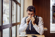 Good-looking young businessman sitting in coffee shop on a coffee break and blowing his nose.