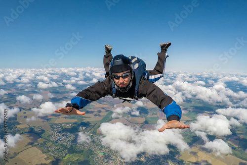 Fotografie, Obraz Male skydiver falling above the clouds
