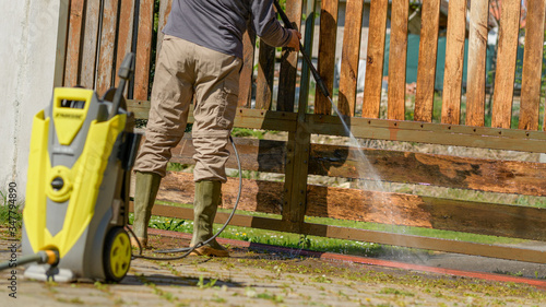 Fotografija Unrecognizable man cleaning a wooden gate with a power washer