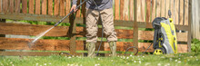 Unrecognizable Man Cleaning A Wooden Gate With A Power Washer. High Water Pressure Cleaner  Used To DIY Repair Garden Gate. Web Banner.