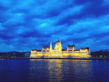 Hungarian Parliament Building By Danube River Against Cloudy Sky