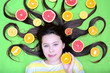 canvas print picture - A cheerful young girl lies with citruses in her loose hair, holds a circle of orange in her hands and licks her lips. Top view