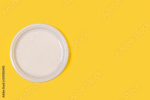 Photo Plato redondo blanco de plástico desechable sobre fondo amarillo liso brillante y aislado