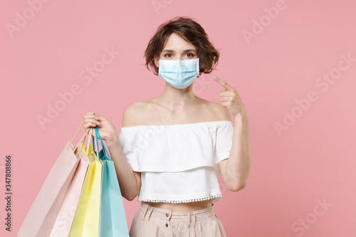 Fotografía Young woman girl in summer clothes hold package bag with purchases isolated on pink background studio