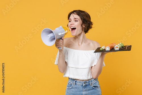 Young woman hold in hand makizushi sushi roll served on black plate japanese food scream in megaphone announces discounts sale isolated on yellow background studio portrait Wallpaper Mural