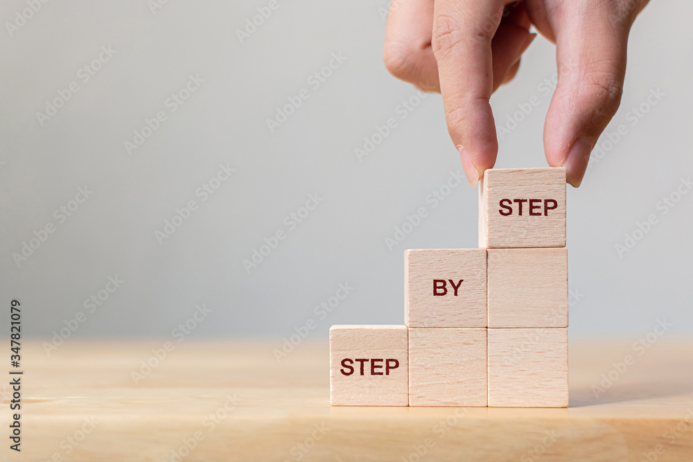 Fototapeta Hand arranging wood block stacking as step stair on top with word Step By Step. Business concept for personal ladder of success process