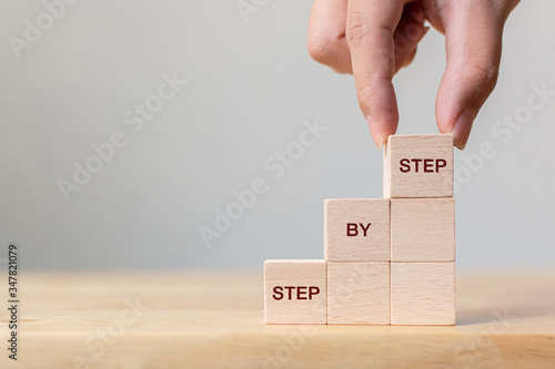 Hand arranging wood block stacking as step stair on top with word Step By Step. Business concept for personal ladder of success process - fototapety na wymiar