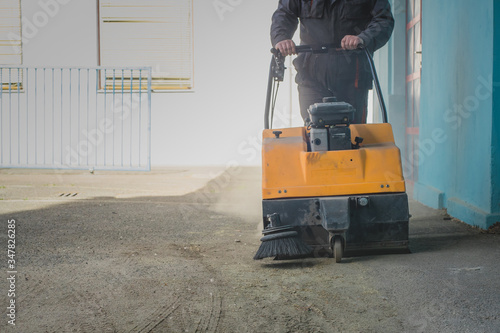 A person is pushing an orange gasoline powered industrial sweeper over dirty asp Wallpaper Mural