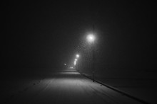 Snowy Street By Illuminated Street Lights Against Clear Sky At Night