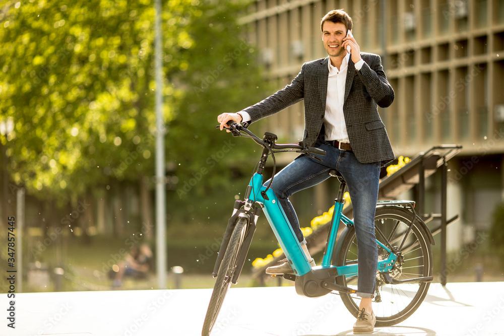 Fototapeta Young businessman on the ebike using mobile phone