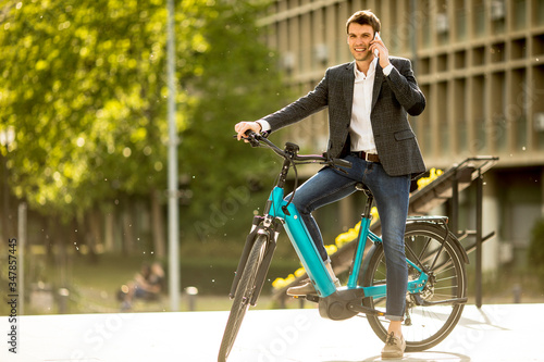 Fototapeta Young businessman on the ebike using mobile phone obraz