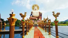 Low Angle View Of Buddha Statue Amidst Pond In Temple Against Sky