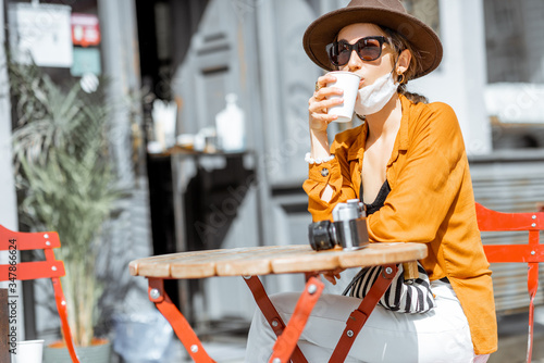 Young woman in facial mask sitting on the cafe terrace alone. Concept of social distancing and new social rules after coronavirus pandemic.