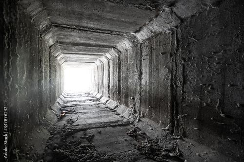 Fotografija Empty square concrete tunnel with light in the end
