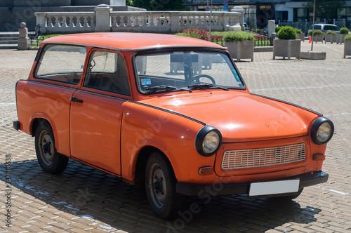 Orange colored vintage restored Trabant car on paved street