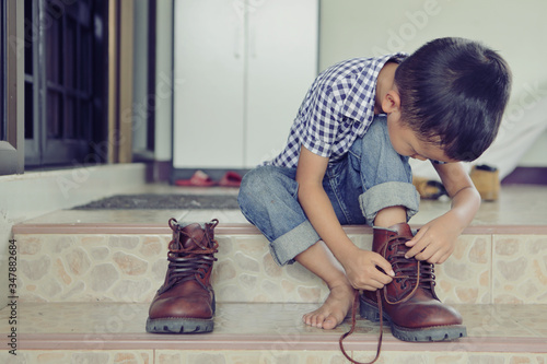 Fotomural An Asian boy is trying on his father shoes.
