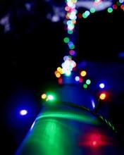 Close-up Of Illuminated Multi Colored Christmas Lights On Railing