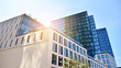canvas print picture - Bottom view of office building window close up with sunrise, reflection and perspective. Modern architecture with sun ray. Glass facade on a bright sunny day with sunbeams on the blue sky.