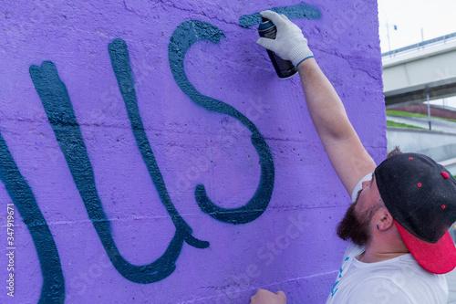 Graffiti artist painting with aerosol spray bottle Wallpaper Mural