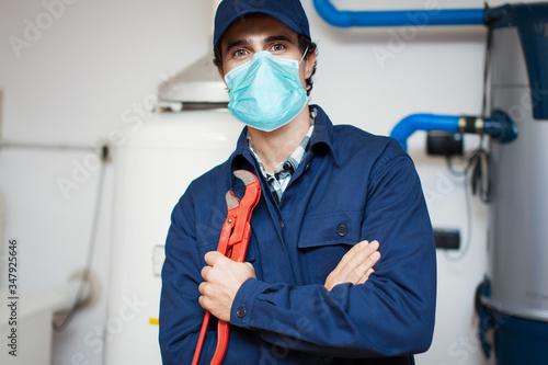 Smiling technician repairing an hot-water heater wearing a mask, coronavirus con Canvas Print