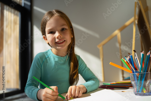 Valokuvatapetti Cheerful little girl drawing with colored pencil at home