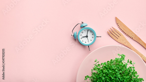 Leinwand Poster Alarm clock, cutlery and plate with greenery on pink