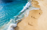 Fototapeta Fototapety z morzem do Twojej sypialni - People on the beach on Bali, Indonesia. Vacation and adventure. Beach and large waves. Top view from drone at beach, azure sea and relax people. Travel and relax - image