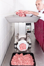 Butcher Grinding Meat In Shop