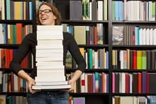 Woman Carrying Stack Of Books ...