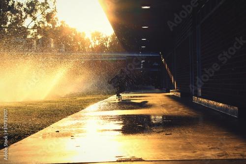 Person Skateboarding On Wet Sidewalk While Water Sprinkling In Park