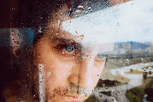 Closeup Of Sad Desperate Young Man Looking Away Through Wet Window While Staying In Self Isolation At Home Because Of Coronavirus