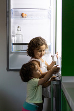 Little Girl And Toddler Taking Fresh Yoghurt From Fridge While Stealing Food At Night At Home Together