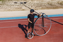From Above Serious Man In Black Activewear And Helmet Looking Away While Standing With Retro Penny Farthing Bicycle On Racetrack At Sports Ground