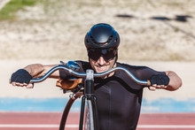 Portrait Of Happy Man In Black Activewear And Helmet Looking At Camera While Standing With Retro Penny Farthing Bicycle On Racetrack At Sports Ground