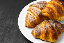 Top View On Three Fresh French Buttery Croissant On A White Plate On A Black Background With Copy Space