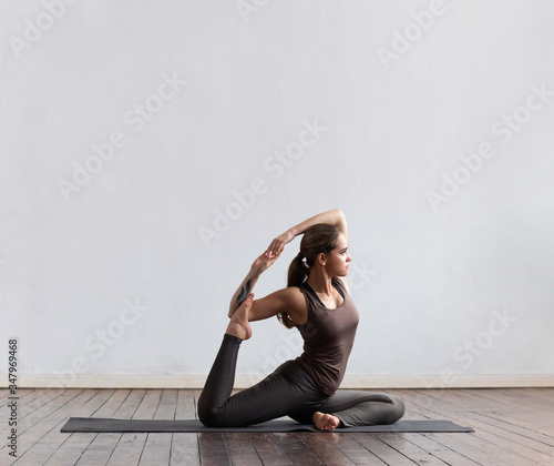 Fototapety, obrazy: Young and fit woman practicing yoga indoor in the class. Stretching exercise in the day light. Sport, fitness, health care and lifestyle.