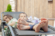 Upset Children With Children's Bare Feet On A Chaise Longue. A Boy And A Girl Are Resting In The Sun. The Concept Of Relaxation.