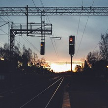Railway Signals By Railroad Tracks Against Cloudy Sky At Sunset