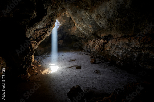 Sunlight shines from above into a small cave in the Mojave desert, California, USA