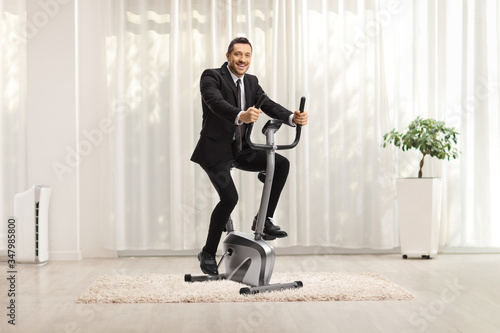Fotomural Businessman on an exercise bike at home