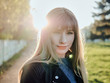 Close up headshot of adorable blonde haired charming smiling woman with blue eyes looking into camera and adorable smile in city park with bright sun flare evening