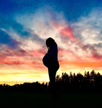 Silhouette Pregnant Woman Standing Against Cloudy Sky During Sunset