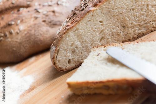 Fotografia Pane appena sfornato con fetta in primo piano / Freshly baked bread with slice i