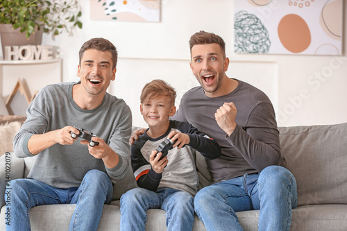Happy gay couple with adopted child playing video game at home Canvas Print