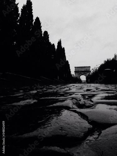 Fotografie, Obraz Wet Cobblestone Street Leading Towards Arch Of Titus Against Sky