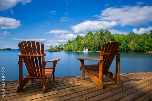 Two Muskoka chairs sitting on a wood dock facing a calm lake Fototapeta