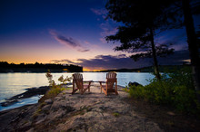 Two Muskoka Chairs Sitting On A Rock Formation Facing A Calm Lake At Dusk In Cottage Country.