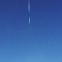 Low Angle View Of Contrails At Blue Sky