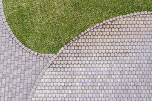 Aerial Top View Of Gray Cobblestone Pavement Footpath With Green Grass Texture Around Stones